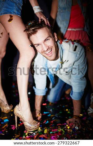 Handsome guy by legs of girl having fun in night club - stock photo
