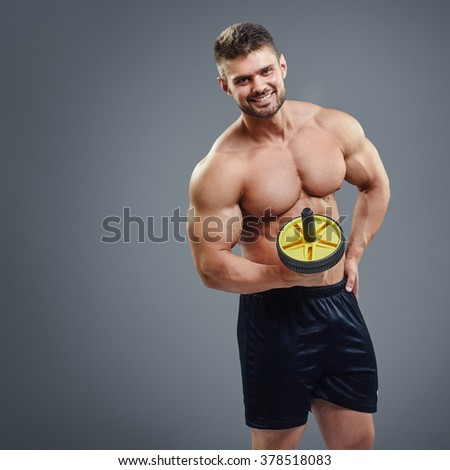 Handsome guy fitness trainer isolated on grey background - stock photo