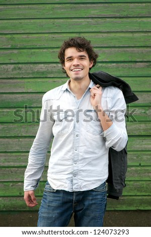 Handsome guy holding his jacket over his shoulder outdoor.  Smile expression on his Face. - stock photo