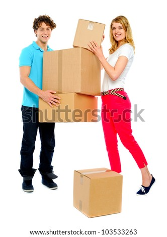 Handsome guy holding stack of cardboard boxes while woman doing the placement - stock photo