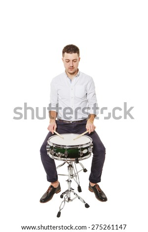 Handsome guy in a white shirt teaches properly play the drums on a white background - stock photo