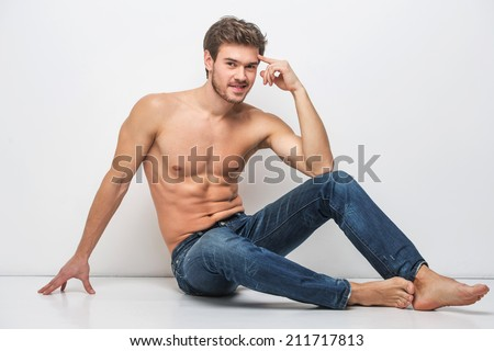 Handsome guy in jeans with bare torso. man sitting on floor near wall  - stock photo