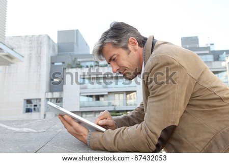 Handsome guy in town using electronic tablet - stock photo