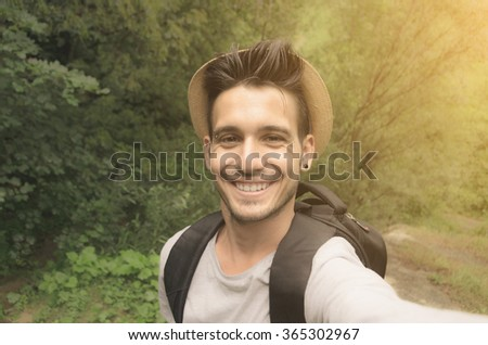 Handsome guy is taking a selfie with his smartphone in the nature - caucasian people - people, lifestyle and technology concept - stock photo