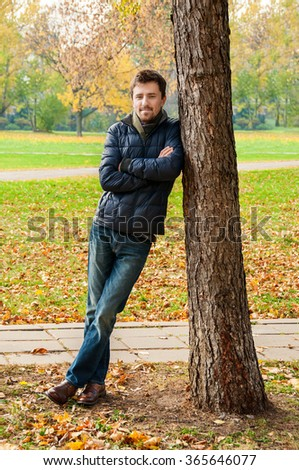 Handsome guy leaned against a tree in autumn park - stock photo