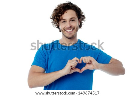 Handsome guy making heart shape with his hands - stock photo