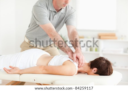 Handsome Guy massaging a cute woman's neck in a room - stock photo