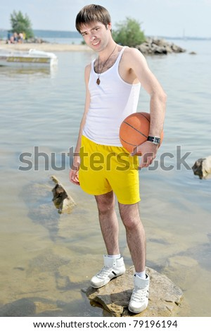 Handsome guy standing on the rocky beach in water holding a basketball ball - stock photo