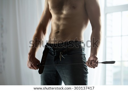 Handsome guy topless with whip BDSM - stock photo