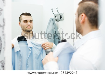Handsome guy trying on new shirt at apparel store  - stock photo