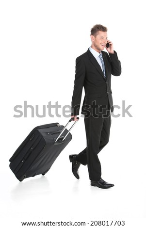 handsome guy walking with luggage in suit. man talking on phone on white background - stock photo