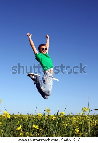 Handsome guy with glasses jumps on the field - stock photo