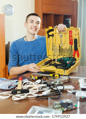 Handsome guy with working tools at home - stock photo