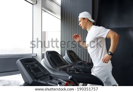 Handsome gym man running on the treadmill - stock photo