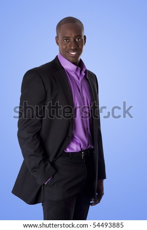 Handsome happy African American corporate business executive man smiling, wearing black suit with purple shirt, standing with authority with hand in pocket,  isolated. - stock photo