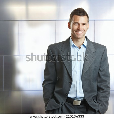 Handsome happy confident caucasian businessman hands in pocket, suit with no tie. Smiling, standing, looking at camera, - stock photo