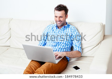 Handsome happy man browsing Internet on his laptop - stock photo