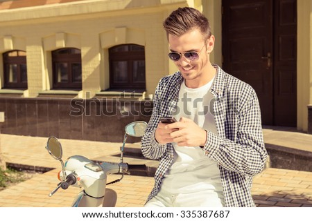 Handsome happy man sitting on the motorbike typing a message on the phone - stock photo