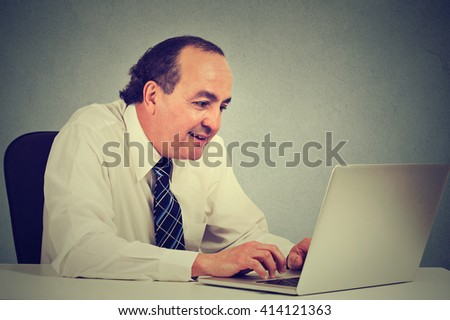 Handsome happy middle aged businessman working with laptop in office - stock photo