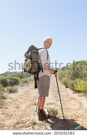 Handsome hiker smiling at camera in the countryside on a sunny day - stock photo