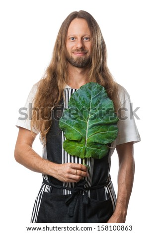Handsome hippie man holding a kale leaf over his heart as a concept for good health. Isolated on white. - stock photo
