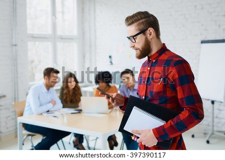 Handsome hipster, designer standing in the office with his smartphone - stock photo