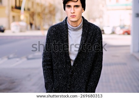 Handsome hipster is walking down the street - stock photo