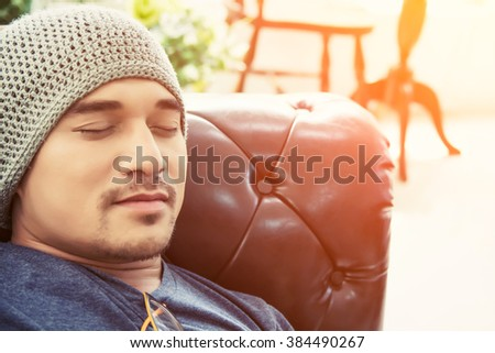 handsome hipster man take a nap on his sofa in the house - stock photo