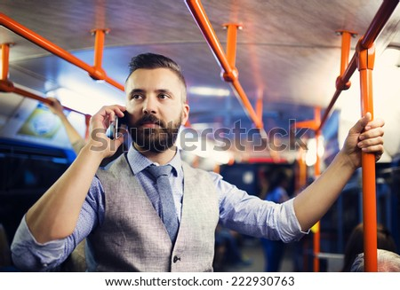 Handsome hipster modern man calling by mobile phone in tram in night - stock photo