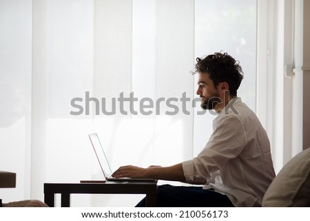 handsome hipster modern man designer working home using laptop at home - stock photo