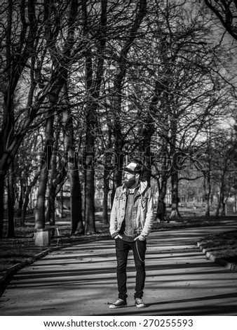 Handsome hipster modern man in the park, black and white - stock photo