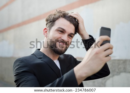 handsome hipster modern man using smart phone selfie in the city - stock photo