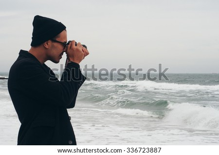 handsome hipster photographer traveler tourist guy wearing glasses and hat taking photo of hazy cold sea with his film camera  - stock photo