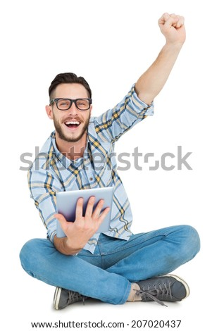 Handsome hipster using tablet pc and cheering on white background - stock photo