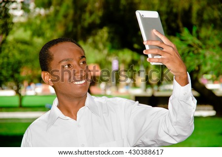 Handsome hispanic black man wearing white shirt in outdoors park area holding up tablet and watching screen as in taking selfie - stock photo