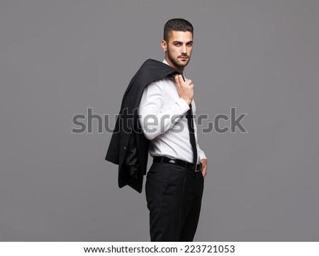 handsome hispanic elegant man in black suit on grey background, holding the coat over his shoulder - stock photo
