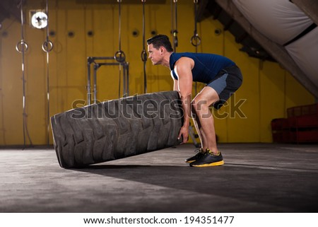 Handsome Hispanic man flipping a big tire in a gym - stock photo