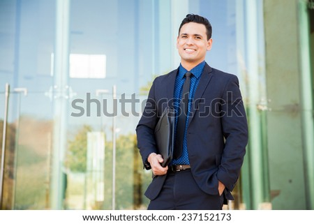 Handsome Hispanic man in a suit carrying his resume and waiting for a job interview and smiling - stock photo