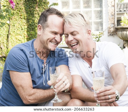Handsome homosexual couple sitting laughing outdoors with glasses of champagne - stock photo