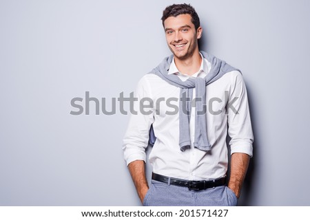 Handsome in style. Cheerful young man in smart casual wear looking at camera and holding hands in pockets while standing against grey background - stock photo