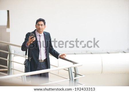 handsome indian business executive working on smart phone in office - stock photo