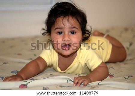 Handsome Indian kid learning to crawl on the bed - stock photo
