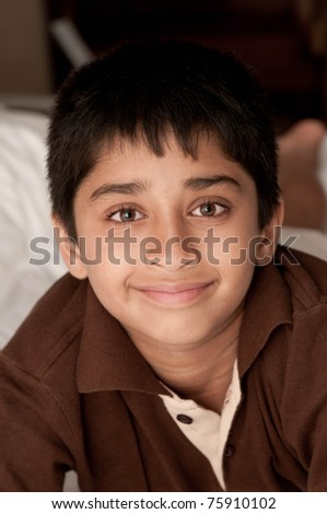 Handsome Indian kid lying happily on the bed - stock photo