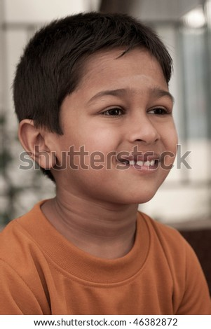 Handsome Indian kid smirking in front of the camera - stock photo