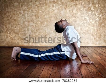 Handsome Indian man in white shirt doing bhudjangasana back bending cobra pose indoors on wooden floor at grunge background - stock photo