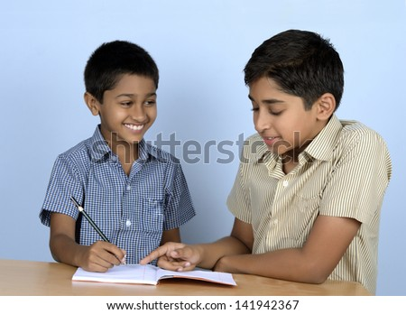 Handsome Indian toddler being coached by his brother - stock photo
