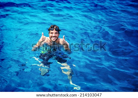 Handsome instructor of swimming wearing goggles in the pool, having fun in the water, summer adventure, travel and vacation concept - stock photo