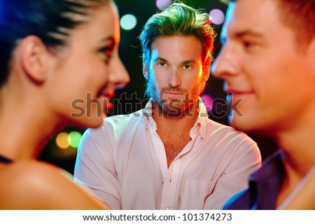 Handsome jealous man looking at flirting couple on dance floor. - stock photo