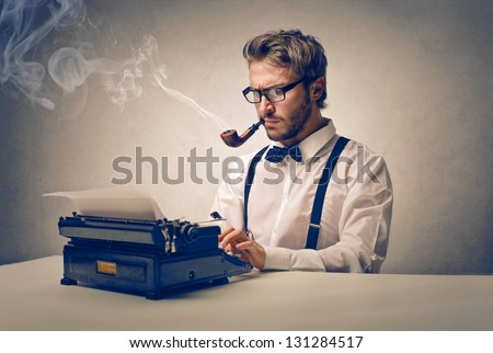 handsome journalist writing with typewriter - stock photo