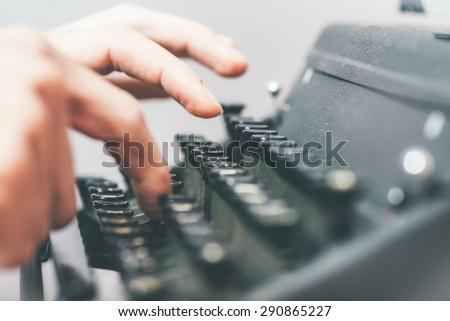 handsome journalist writing with typewriter - stock photo